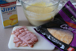 Corn bread mix in a clear mixing bowl, with a bag of shredded cheese, along side chopped ham on a cutting board.
