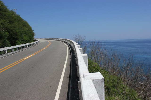 A view of the highway adjacent to the coastline and a view of the vast blue ocean.