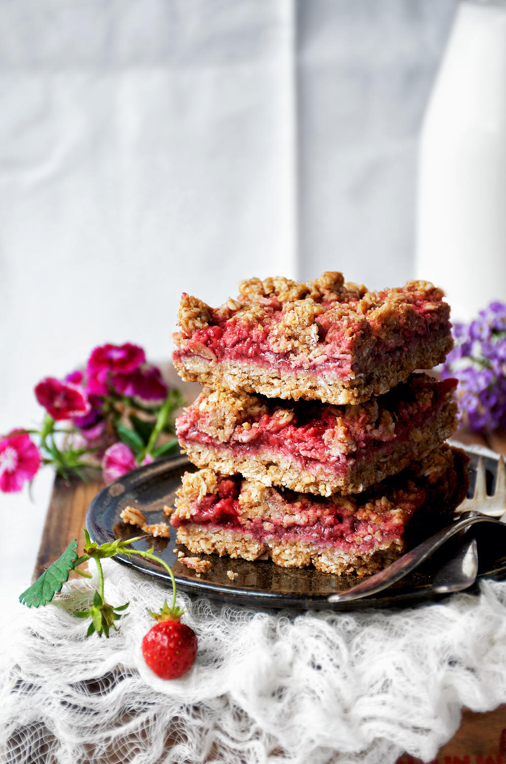 Vegan and gluten free strawberry crumble bars with an oat base and streusel, lots of seasonal berries, and a little coconut sugar for sweetness. These bars are great for an on the run breakfast or snack, and equally good served with ice cream as a healthier dessert.