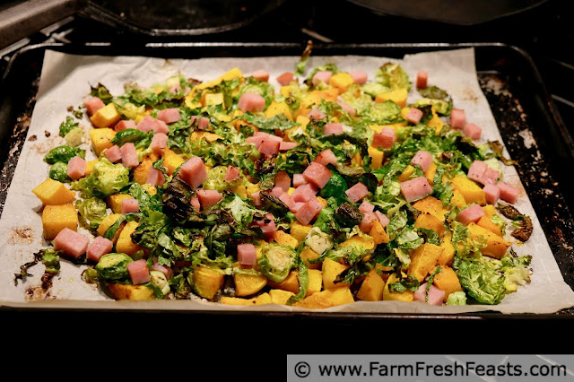 image of baking pan covered with roasted butternut squash cubes, shredded brussels sprouts, and leftover ham cubes