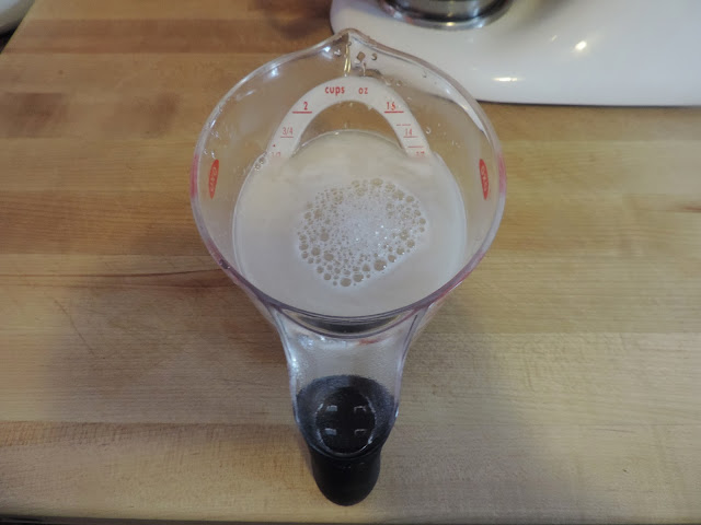 A measuring cup, sitting on a counter, with yeast blooming in it.