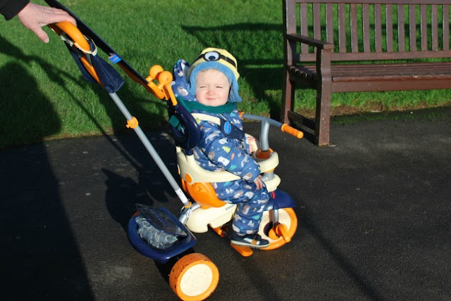 toddler on bike with eyes shut because of the sun