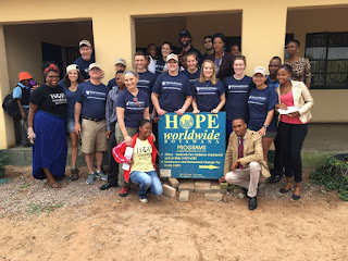SU group poses together with Hope Worldwide sign