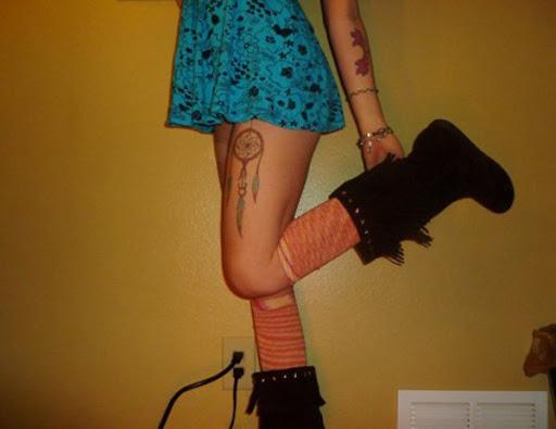 Um dreamcatcher tatuagens para a menina na perna, seu olhar sexy