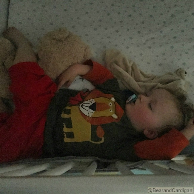 toddler fast asleep in a cot