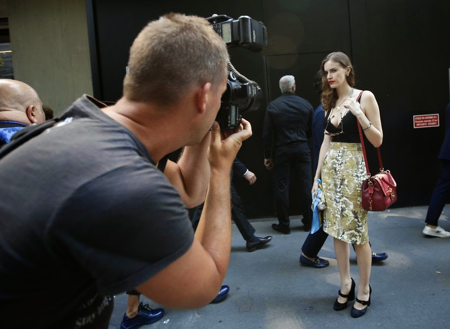 A model is pictured by a street photographer outside the Metropole theatre at the end of the Dolce & Gabbana men's Spring-Summer 2015 show, part of the Milan Fashion Week, unveiled in Milan, Italy, Saturday, June 21, 2014.