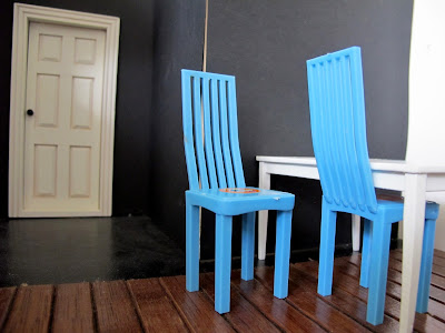 Two blue plastic modern miniature dolls house chairs, at a white table against a black wall and wooden floor.