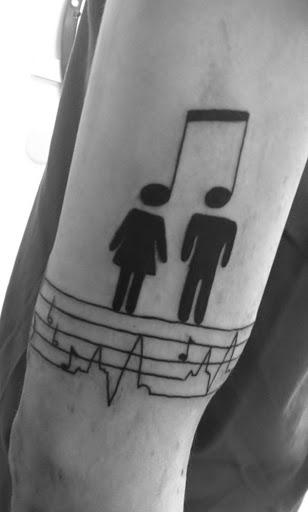 Uma nota musical cria a cabeça para um par de simplificado representações de pessoas que estão acima de um conjunto de bares musicais neste inspirada tatuagem.