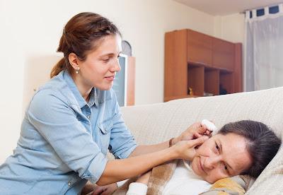 Hija adulta goteando gotas para los oídos a la madre madura