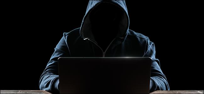 قراصنة مقنعين أمام جهاز الكمبيوتر