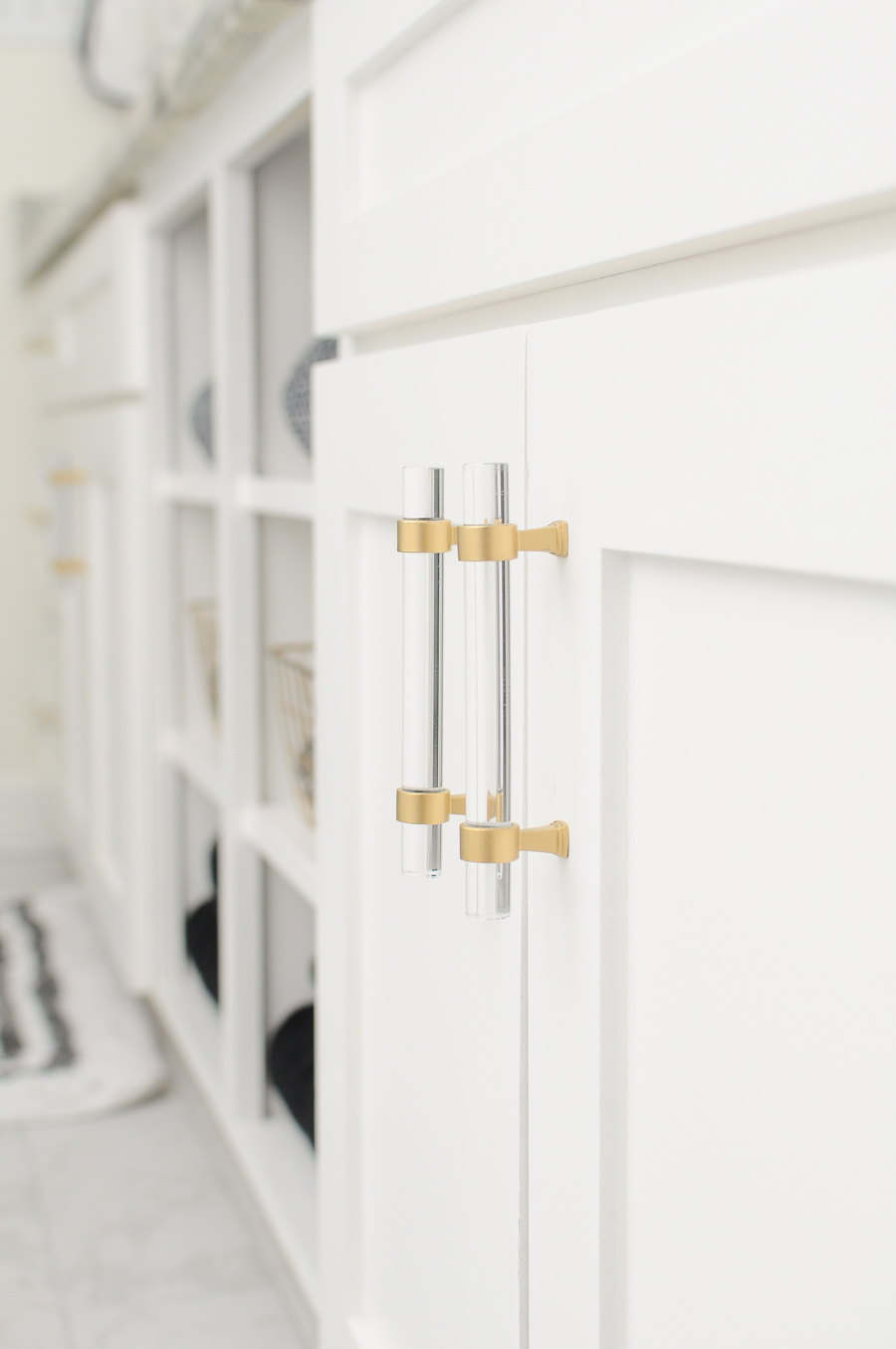 These gold or brass lucite pulls look fabulous against the white shaker cabinets in this master bathroom suite.