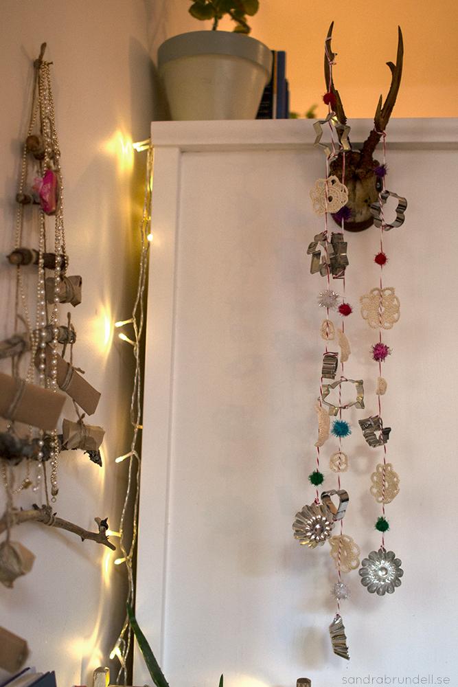 Julpynt av kakstansar, virkade cirklar, snöre, och pompomer.