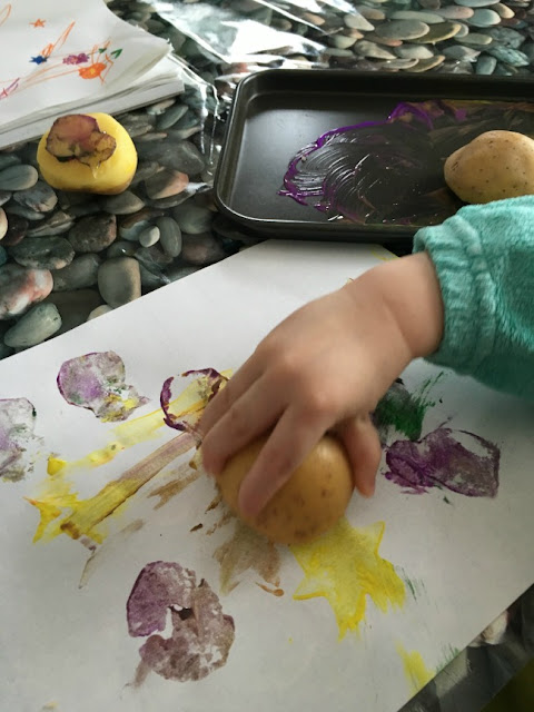 toddlers hand holding potato pressing onto a sheet of paper with potato printing on it