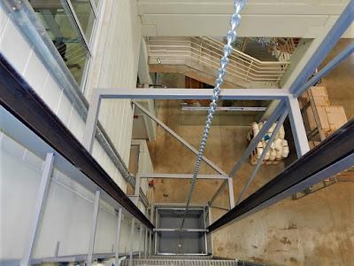 O elevador monta carga interliga o pavimento térreo de contrapiso de concreto armado aos pavimentos de estrutura metálica desmontável.