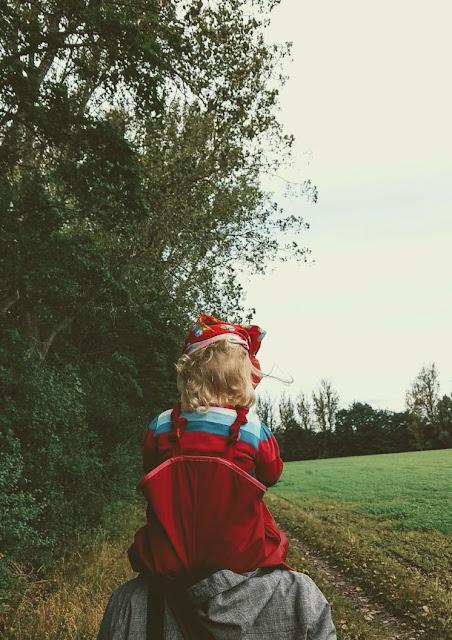 Das Herbstmädchen auf dem Rücken ihres Papas