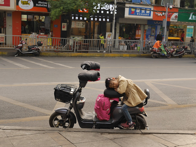 girl resting while sitting on the back of a parked motor scooter