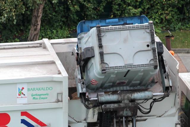 Un camión recoge la basura de un contenedor