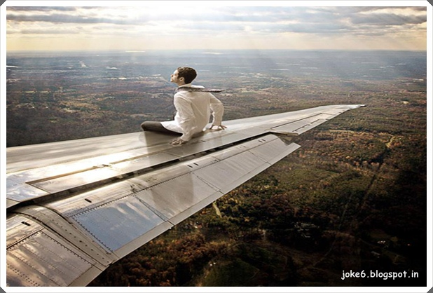 Funny Pic  Without ticket around the world.   A man sitting on a airplane wing trying to journey around the world.