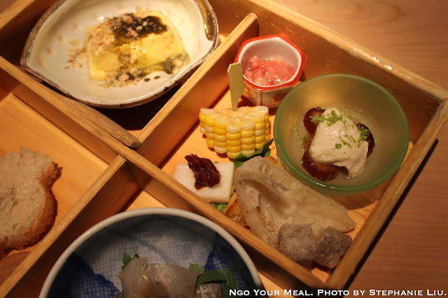 Bento Box: Sesame Tofu with Organic Dates and Sapodilla with Lime Zest; Fried Kisu and Konyaku; Mountain Yam with Soy Beans; Corn on the Cob; Japanese Yam Cake; Skipjack Tuna Innards Marinaded in Honey, Mirin, and Sake for 6 Months at NAOE