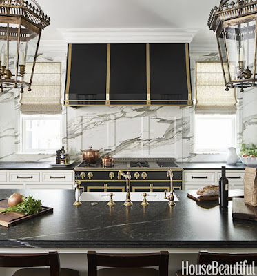 White marble on the walls, pietra cardosa counter tops and black stove