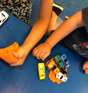two kids playing with orange dough and toy cars