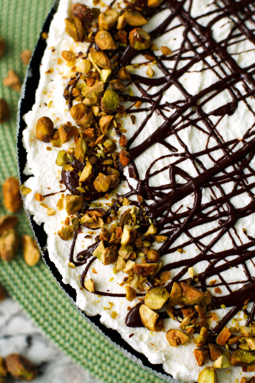 This Pistachio Pudding Pie is a no-bake dessert with an Oreo cookie crust, a creamy pistachio filling, fresh whipped cream, and a pretty chocolate drizzle. It is perfect for parties and picnics!  #nobake #pie #dessert