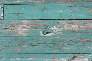 Faded green peeling deck paint revealing weathered wood