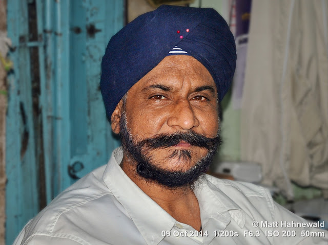 Matt Hahnewald Photography; Facing the World; photo; image; closeup; street portrait; headshot; indoor; world cultures; cultural; one person; character; personality; people; male; adult; powerful; strong; turban; Sikh; human; human face; human head; eyes; handsome; eye contact; photography; consent; empathy; rapport; portrait; portraiture; environmental portrait; travel portrait; travel destination; colour; 4 : 3 aspect ratio; horizontal format; posing; Thailand; Bangkok; Asia; Southeast Asia; Nikon D3100; Nikkor AF-S 50mm f/1.8G; prime lens; 50 mm; travel; religion; en face; front view; city dweller; tradition; manly; facial expression; blue turban; Phra Nakhon District; ethnic; ethnic minority; Gurudwara Siri Guru Singh Sabha; Little India