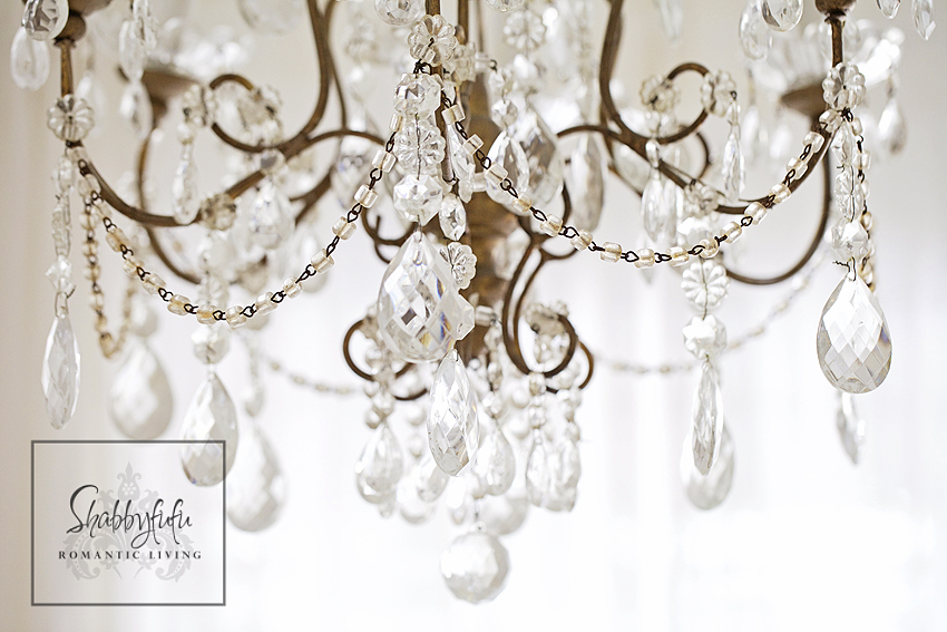 romantic room designs - shining details on a vintage crystal and brass chandelier