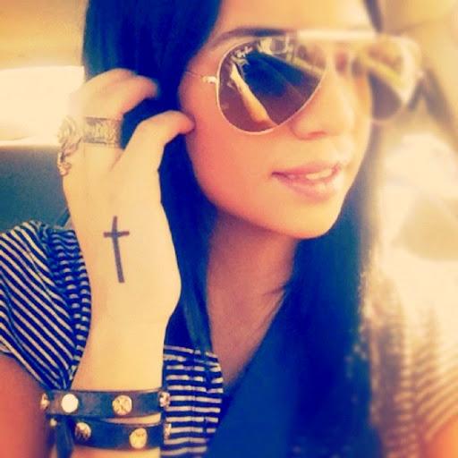 vemos a una chica con tatuaje de cruz en la mano