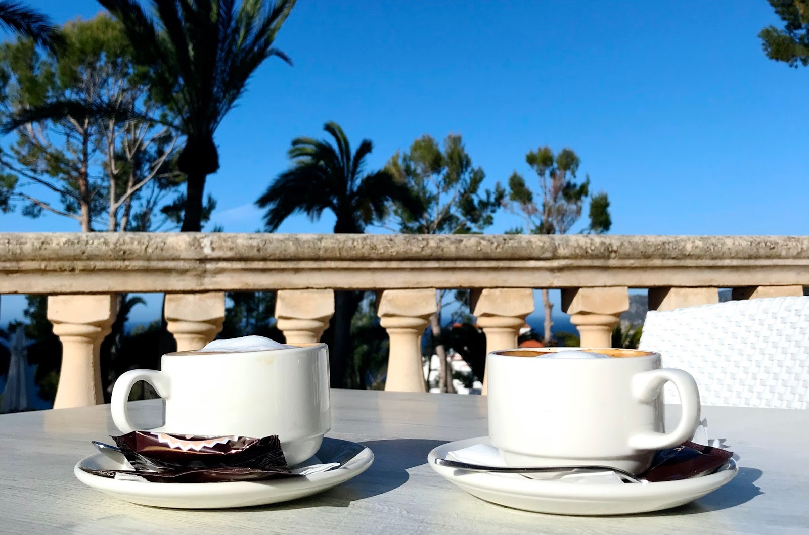 two cups of coffee on a terrace with palm trees