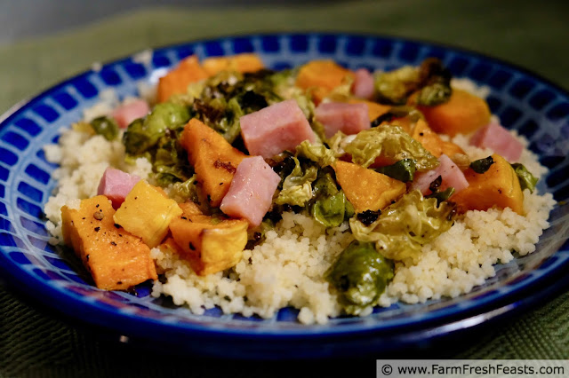 a plate of roasted butternut squash, brussels sprouts, and ham atop a bed of cous cous