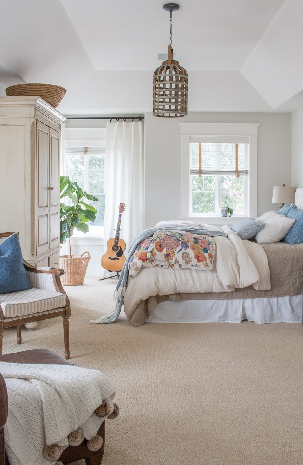 light and neutral bedroom with floral duvet and guitar on a stand
