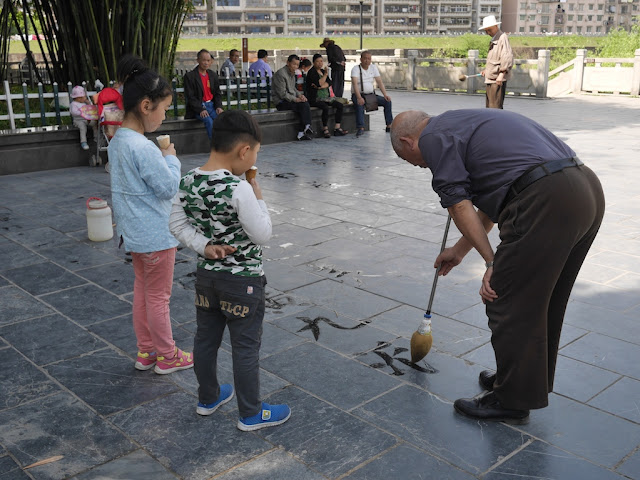 two children eating ice cream watching a man do water calligraphy