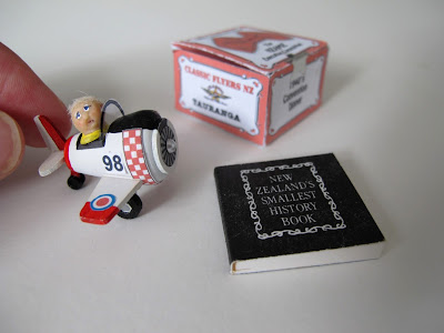Ornament of a boy in a pedal plane, with a miniature book next to it. A hand shows scale.