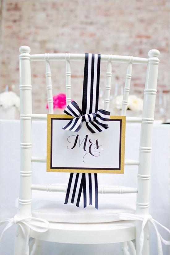 Silla decorada con un cartel en tonos oro y lazo blanco y negro al más puro estilo chic francés
