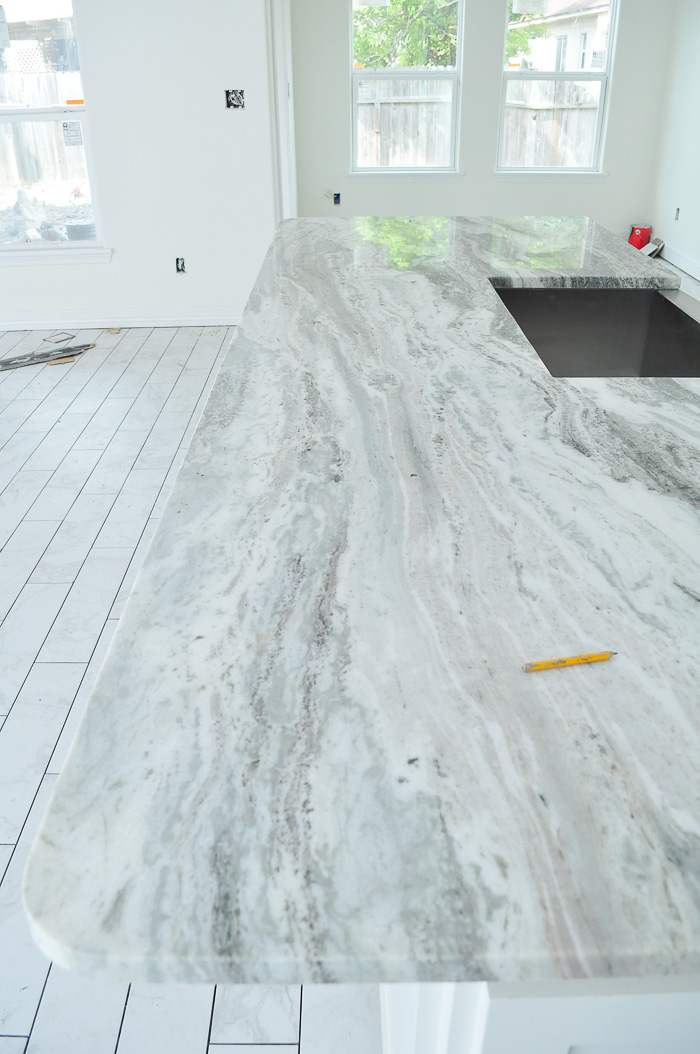 Marble look tile flooring in a white kitchen with shaker cabinets and fantasy brown granite.   via monicawantsit.com