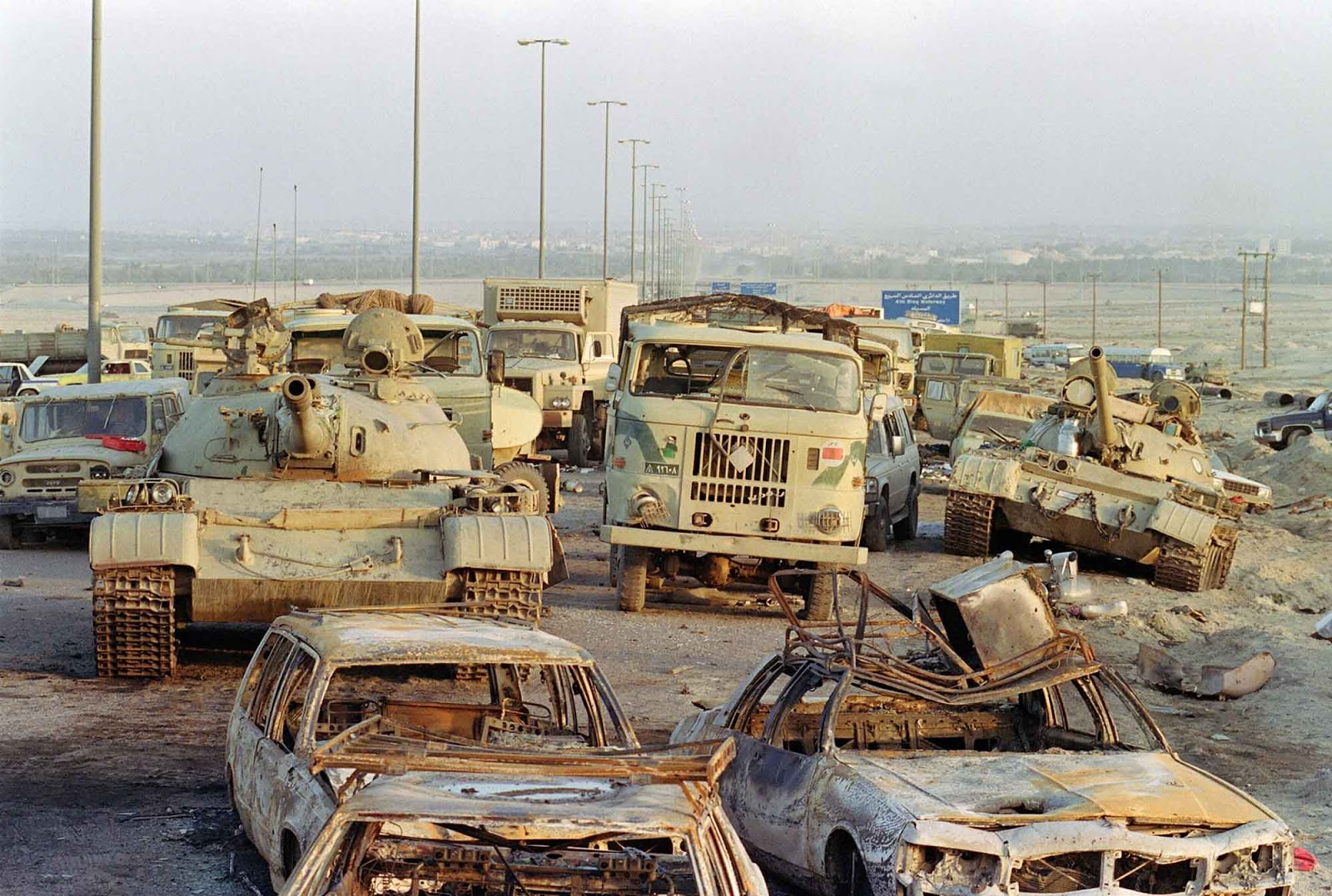 A long line of vehicles, including destroyed Iraqi Army Russian-made T-62 tanks and trucks stand abandoned by fleeing Iraqi troops.