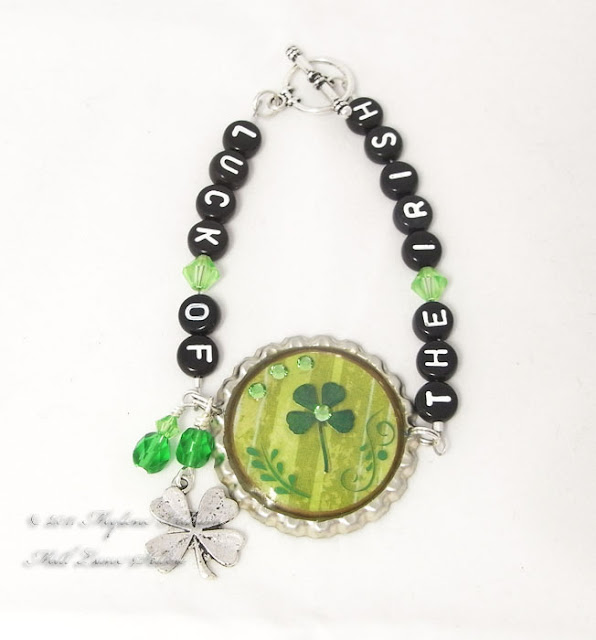 Bottle cap bracelet featuring a 4 leaf clover, light green crystals and green flourish rub ons. The bracelet is strung with alphabet beads spelling out Luck of the Irish.