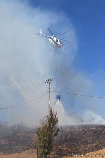 A helicopter with monsoon bucket helped  Fire Service firefighters fight a grass fire on Waimarama Rd, Havelock North, just past Tukituki Rd turn-off. photograph