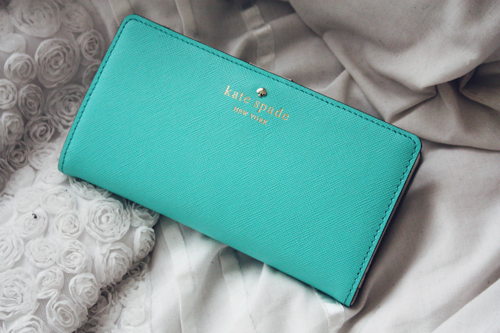 kate spade mikas pond stacy wallet in tiffany blue lying on a white embroidered duvet