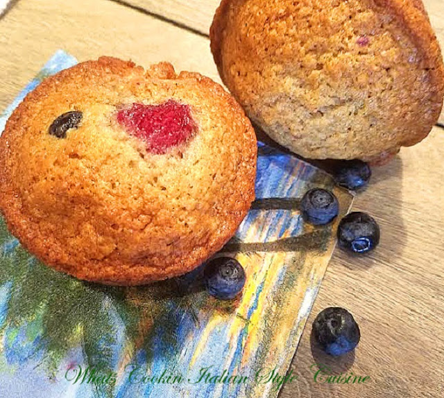 these are Summer Berry Muffins are a quick bread with banana, raspberries and blueberries. Golden brown sweet muffins with fresh fruits and on a tropical palm tree plate