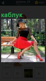 На скамейке сидит женщина в красной юбке и красных туфлях на каблуках