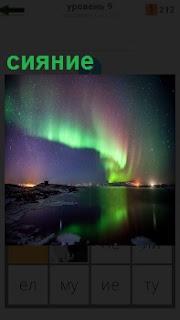 В небе над морем и холмами красивое северное сияние в разных красках