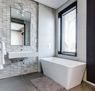 Bathtub with window, bathroom sink with mirror above and towels.