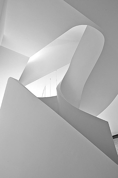 In einem weißen Loft spielt eine geschwungene Treppe die Hauptrolle.