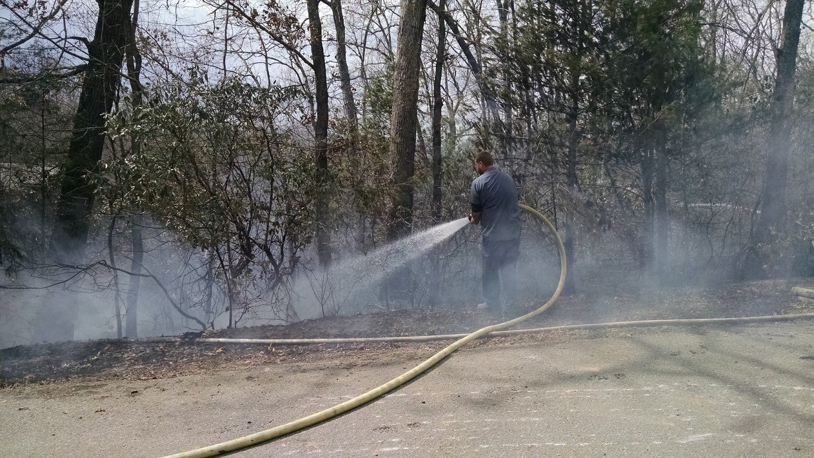 A firefighter applying water to put out hotspots