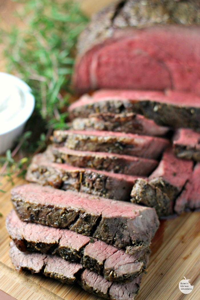 Garlic Herb Beef Tenderloin Roast with Creamy Horseradish Sauce | by Renee's Kitchen Adventures on platter with fresh rosemary garnish and a bowl of creamy horseradish sauce to the left