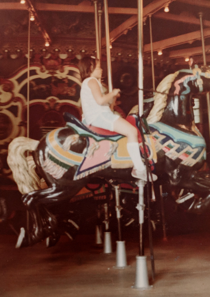image of me as a little kid in profile on a carousel as it circles by the photographer, who was either my mom or grandfather