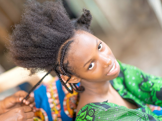 African woman making her hair
